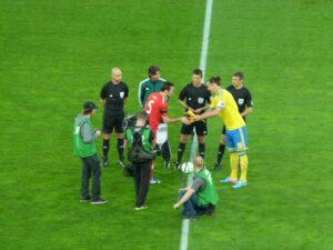 Christian Fuchs begrüßt Zlatan Ibrahimovic vor den Augen des italienischen Schiedsrichter-Trios. Foto: oepb