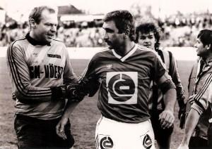 Erwin Fuchsbichler (links) verabschiedet seinen alten Kumpel Hans Krankl (Bildmitte) aus dem Linzer Stadion. Das Spiel zwischen VÖEST und RAPID endete am 24. November 1984 mit 2 : 2. Krankl, der in dieser Partie einen Jochbeinbruch erlitt, bezwang Fuchsi zwar aus dem Spiel, scheiterte jedoch einmal anhand eines Elfmeters. Dahinter im Bild der junge Jürgen Werner.