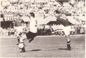 Josef Huegi (rechts, Nr. 18) erzielt einen seiner drei Treffer. Ernst Happel (Nr. 3) kommt zu spät.