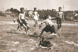 """Kinder beim Kicken mit dem Fetznlaberl auf der """"Gstätten"""" in Döbling 1932. Links die Hohe Warte, rechts im Hintergrund der Karl-Marx-Hof. Foto: ÖNB / Lothar Rübelt"""