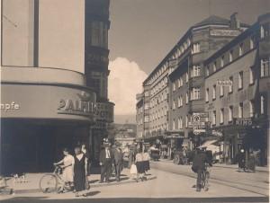 Blick von der Mozartkreuzung auf der Landstraße stehend in die Mozartstraße hinunter im Jahre 1935. PALMERS und die Centralapotheke (links im Bild) gibt es heute noch. Die Tramwaylinie M wurde 1969 durch eine Autobus-Linie ersetzt. Foto: Otto Kaiser / NORDICO Stadtmuseum Linz