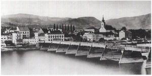 Ein Schiffsunglück des Jahres 1868 bewirkte, dass die seit 1497 bestehende Holzbrücke über die Donau zwischen Linz und Urfahr komplett erneuert wurde. Zwischen 1870 und 1872 wurde der Neubau einer Eisenbrücke auf vier Strompfeilern vorgenommen. Heute steht dort die Nibelungenbrücke. Blick auf die Marktgemeinde Urfahr samt Stadtpfarrkirche. Foto: Sammlung oepb