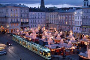 Der winterliche Hauptplatz bietet alljährlich eine wundervolle Kulisse für den Linzer Christkindlmarkt. Die Marktstände sind mit Motiven von Linzer Sehenswürdigkeiten bemalt und symbolisieren mit ihren geschwungenen Vordächern die Wellen des Donaustroms. Foto: Stadt Linz