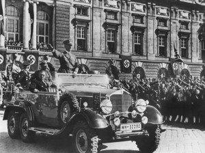 Adolf Hitler erreicht am 15. März 1938 den Wiener Heldenplatz, wo er von Tausenden Österreichern begeistert empfangen und bejubelt wird. Hier vollzog er die Eingliederung des damaligen österreichischen Ständestaates in das Großdeutsche Reich. Neben dem stehenden Hitler im Mercedes sitzend der spätere Bundeskanzler Dr. Arthur Seyss-Inquart. Foto: ÖNB