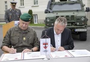 Brigadier Nikolaus Egger (links) und Bürgermeister Stefan Karlinger unterzeichnen die Partnerschaftsurkunden. Foto: Bundesheer / Simader