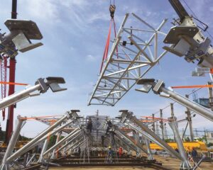 Ein Baukran positioniert einen Bodenträger über dem Stahlstützensystem, das mit angeflanschten Isokorb Elementen des Typs KST zur thermischen Trennung versehen ist, welche Wärmeverluste verhindern und gleichzeitig die Last der gesamten EACF-Einrichtung tragen. Foto: Afaconsult / Estúdio 41