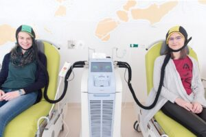 Zwei junge Besucherinnen probieren im St. Josef Krankenhaus Wien aus, wie sich eine Kühlhaube anfühlt. Damit kann der Haarausfall bei einer Chemo reduziert werden. Foto: Peter Rösler