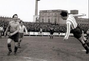 Spielszene zwischen dem FC Wien (gestreiftes Trikot) und der Vienna (1 : 1) vom Frühjahr 1951. 6.000 Zuschauer waren auf dem FC Wien-Platz zugegen. Im Hintergrund erkennt man die Wiener Holzwerke, sowie die Heller-Süßwarenfabrik. Foto: oepb