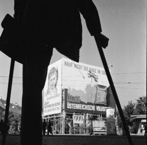 Ein Bild, das bis in die späten 1980er Jahre hinein keine Seltenheit war: Kriegsversehrte nämlich. Hier beim Betrachten eines Wahlplakats der ÖVP zu den Nationalratswahlen in Wien 1949. Foto: Okamoto / ÖNB