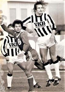 """Der Linzer ASK, im Volksmund kurz LASK genannt, befindet sich seit längerem auf einem sportlichen Höhenflug. Nach jahrzehntelangem Kümmerdasein in der zweiten und sogar dritten Leistungsklasse, wandelt der derzeitige Kader der """"Landstraßler"""" auf den Spuren der seinerzeit überaus erfolgreichen Vorgänger. Der einstige LASK-Meisterfußballer von 1964/65, Johann Kondert führe als Coach die Schwarz-Weißen in den Jahren 1984 bis 1987 viermal en suite in den UEFA-Cup-Bewerb. Der LASK war damals hinter dem FK Austria Wien und dem SK RAPID Wien die starke dritte Kraft in Österreich. Derzeit ist es wohl so, dass der LASK das Pech hat, dass es den FC Red Bull Salzburg gibt, denn ohne diesen Liga-Krösus könnte man sich durchaus berechtige Chancen auf den zweiten Titelgewinn in der über 111-jährigen Vereinsgeschichte ausrechnen. Und auch vor 40 Jahren sorgte der LASK für Furore. Als Bundesliga-Aufsteiger im Sommer 1979 hielten die Athletiker die gesamte Saison 1979/80 ohne großartige sportliche Krise durch, eilten teilweise von Erfolg zu Erfolg, und beendeten die Spielzeit als Saison-Dritter. Auch gegen den großen Rivalen und Saison-Favoriten aus der gleichen Stadt, den SK VÖEST Linz, der übrigens Vize-Meister wurde, blieben die Schwarz-Weißen in vier Derbys ungeschlagen – bei zwei Siegen und zwei Remis. Hier eine Spielszene vom Samstag, 27. Oktober 1979. Der spätere ÖFB-Teamchef Dietmar Constantini (LASK, rechts) bleibt gegenüber seinem Gegenspieler Alberto Martinez (SK VÖEST Linz) obenauf. Im Hintergrund beobachtet Gert Trafella (LASK) den Zweikampf. Aus SK VÖEST Linz vs. Linzer ASK, 1 : 2 (Pausenstand 1 : 1) vor 21.000 Zuschauern im Linzer Stadion auf der Gugl. Quelle und Foto: oepb"""