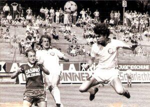 """""""Fußball im Backofen!"""" Es war alles schon einmal dagewesen. Die Saison 1982/83 beispielsweise wurde bis in den Frühsommer hinein gespielt und erst am Samstag, 25. Juni 1983 beendet. Die einheitliche Anstoßzeit war 16 Uhr. Sommerhitze bei über 35 Grad machte sich im Glutofen Linzer Stadion breit. Dennoch gaben die Akteure sprichwörtlich alles. Der SK VÖEST Linz gewann sein letztes Meisterschaftsspiel gegen den SV Austria Salzburg mit 3 : 0 (Pausenstand 0 : 0) und vermieste den Mozartstädtern damit die sicher geglaubte UEFA-Pokal-Teilnahme. Da es allerdings für die Linzer Werkself um nichts mehr ging, der 8. Tabellenplatz im ersten Jahr der neuen 16er Liga https://www.oepb.at/allerlei/seinerzeit-im-sommer-1982.html wurde erreicht, verloren sich auch nur knapp 1.000 Zuschauer im Gugl-Oval. Im Bild von links: Ferdinand Bartosch (Salzburg), Wolfgang Paier und Jürgen Werner (beide SK VÖEST). Quelle und Foto: © oepb"""