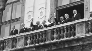 Im Bild von rechts: Bundeskanzler Julius Raab, UdSSR-Außenminister Wjatscheslaw Molotow, Vizekanzler Adolf Schärf (mit weißem Taschentuch in die jubelnde Menge winkend), Österreichs Außenminister Leopold Figl (mit dem unterzeichneten Staatsvertrag), Antoine Pinay (Außenminister Frankreich), sowie der US-Außenminister John Foster Dulles (mit weißem Taschentuch) am Balkon des Schloss Belvedere am 15. Mai 1955. Foto-Sammlung ÖNB