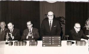 """Der für die Verstaatlichte Industrie zuständige Minister Dr. Bruno Pittermann (stehend) anlässlich der alljährlich stattfinden Sportler-Ehrung des SK VÖEST auf Besuch in Linz in den späten 1960er Jahren. Pittermann, der als glühender Anhänger der Wiener Austria galt, wollte immer erreichen, dass die VÖEST """"seine"""" Austria sponsern würde. Er biss mit diesem Vorhaben in Linz jedoch auf Granit – oder vielmehr auf Stahl. Im Bild von links: VÖEST-Kassier Wilhelm Altenstraßer, Obmann Hans Rinner, VÖEST-Generaldirektor Dr. Herbert Koller, Bruno Pittermann, sowie Generaldirektor-Stellvertreter Dkfm. Johann Grünn. Foto: © oepb"""
