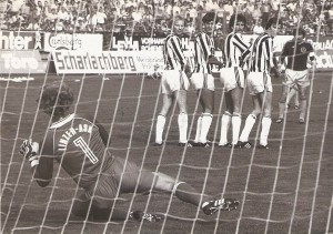 Aus der Bundesliga-Geschichte: Die Saison 1981/82 war nach vier gespielten Runden noch sehr jung, als am 5. Spieltag, einem Samstag, 12. September 1981 um 16 Uhr im Linzer Stadion der LASK und der SK VÖEST Linz zum ersten von insgesamt vier Stadt-Derbys der Saison antraten. Der SK VÖEST galt als Favorit und hätte bei einem vollen Erfolg zur Tabellenspitze aufschließen können. Der LASK startete durchwachsen in die neue Spielzeit und lag in der 10er Liga an der 8. Stelle. Die Gugl war mit 13.500 Zuschauern gut besucht und an jenem Tag auch das Stadion mit den meisten Zuschauern in Österreich. Und es kam, wie es so oft gerade in Derbys immer wieder passiert – der Favorit strauchelte. VÖEST´s Paradestürmer Max Hagmayr war bei Kurt Nagl https://www.oepb.at/allerlei/kurt-wolfgang-nagl-admiraner-im-lask-dress.html in guten Händen und Willi Kreuz, https://www.oepb.at/allerlei/wilhelm-willy-kreuz.html Dreh- und Angelpunkt des SK VÖEST-Spiels scheiterte – wie hier auf dem Schnappschuss aus der 1. Spielhälfte, mehrmals an LASK-Keeper Klaus Lindenberger. Im Bild von links: Klaus Lindenberger, Jupp Bläser, Wolfgang Nagl, Josef Lenhart, Karl Meister (alle LASK), sowie Willi Kreuz (SK VÖEST). Aus LASK gg. SK VÖEST Linz vom 12. September 1981 vor 13.500 Zuschauern im Linzer Stadion, 1 : 0 (Pausenstand 0 : 0). Quelle und Foto: © oepb