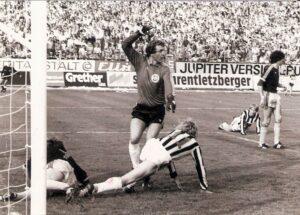 Irgendwann war es dann geschehen. Die wenigen Angriffe der Athletiker waren stets gefährlich und in der 65. Minute auch erfolgreich. Edmund Kaczor, im Sommer 1981 von Rot-Weiß Oberhausen nach Linz gewechselt, gelang in der 65. Minute das Goldtor für seinen neuen Arbeitgeber. Der Treffer war eine deutsch-deutsche Co-Produktion, denn die Flanke kam von Michael Toppel, der im Jahr zuvor aus Berlin von den Amateuren der Hertha zum LASK gewechselt war. Der LASK spielte den Sieg nach Hause, der SK VÖEST hatte in diesem Spiel sein Pulver verschossen. Im Bild von links: Am Boden zerstört Georg Zellhofer, https://www.oepb.at/allerlei/georg-zellhofer-60-jahre-jung-40-jahre-bundesliga.html VÖEST-Keeper Kurt Kaiserseder reklamiert Abseits, Edmund Kaczor (Nr. 11), sowie Michael Toppel (beide LASK) und Alfred Gert (SK VÖEST). Aus LASK gg. SK VÖEST Linz vom 12. September 1981 vor 13.500 Zuschauern im Linzer Stadion, 1 : 0 (Pausenstand 0 : 0). Quelle und Foto: © oepb